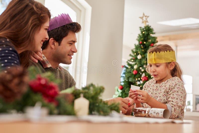Niña linda con los padres que leen su list d'envie de la Navidad fotografía de archivo