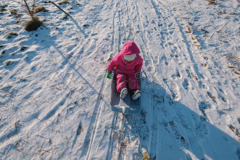 Niña linda con los trineos del platillo al aire libre el día de invierno fotos de archivo