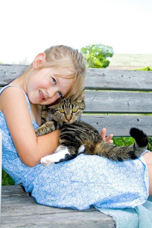 Niña linda con su gato. foto de archivo