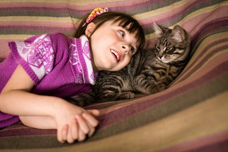 Niña linda con su gato querido imagenes de archivo