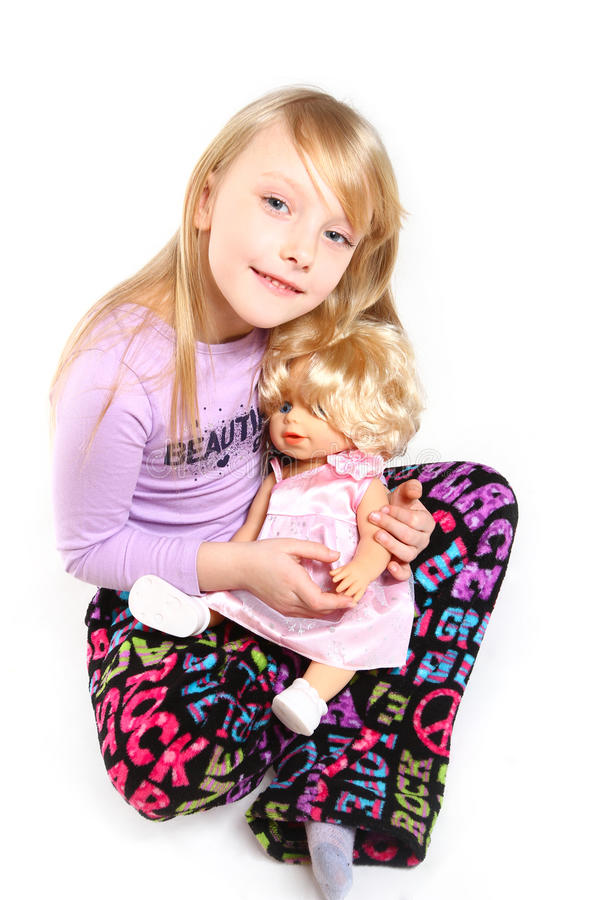 Niña linda con una muñeca que se sienta en el fondo blanco imagenes de archivo