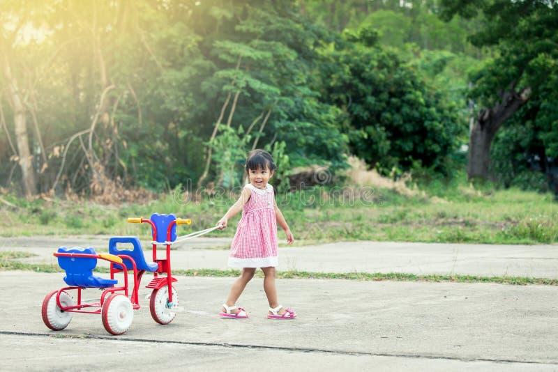 Niña linda del niño que se divierte para tirar de su triciclo foto de archivo