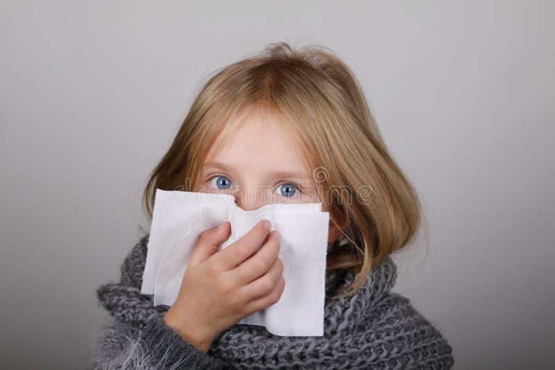 Niña linda del pelo rubio que sopla su nariz con el tejido del papel Concepto de la atención sanitaria de la alergia de la gripe  imagen de archivo