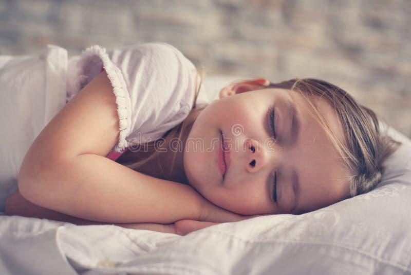 Niña linda en cama imagenes de archivo