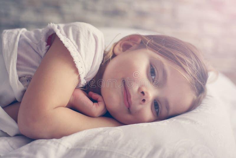 Niña linda en cama foto de archivo