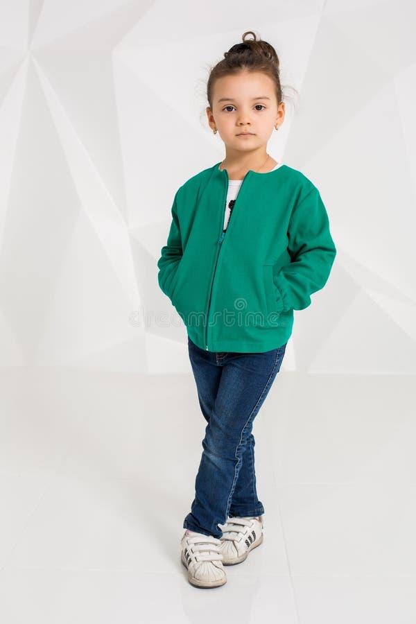 Niña linda en chaqueta verde y vaqueros, manos en bolsillos en el fondo blanco imágenes de archivo libres de regalías