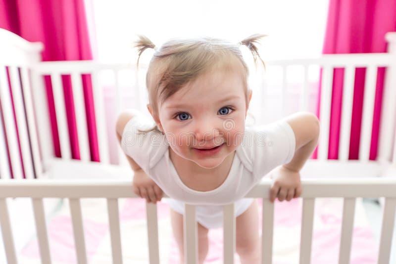 Niña linda en cuna en el sitio del bebé fotos de archivo libres de regalías