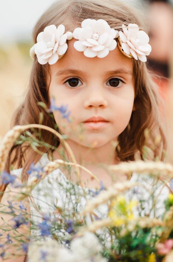 Niña linda en el campo del verano del trigo Un niño con un ramo de wildflowers en sus manos Ciérrese para arriba, retrato fotografía de archivo libre de regalías