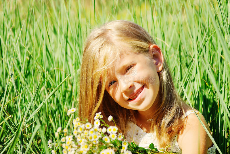 Niña linda en el prado en día de primavera fotos de archivo
