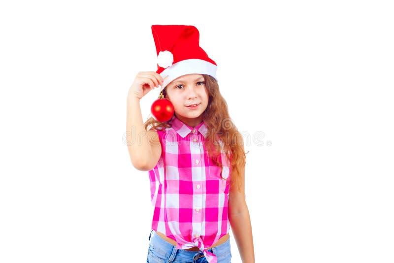 Niña linda en el sombrero de santa que lleva a cabo un juguete del árbol de navidad y un s foto de archivo