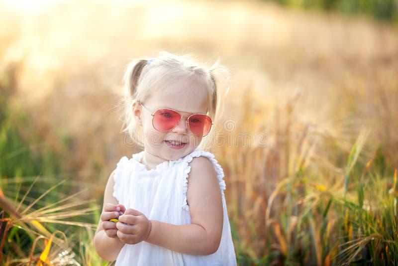 Niña linda en el vestido blanco en el campo del centeno en día de verano foto de archivo
