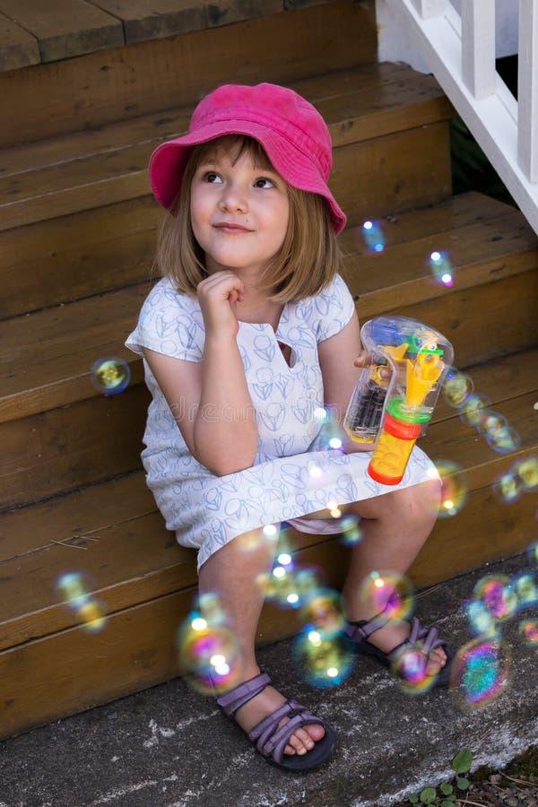 Niña linda en el vestido del verano que se sienta en escaleras con las burbujas de jabón foto de archivo