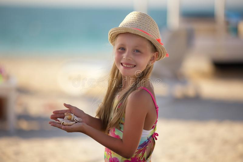 Niña linda en la playa que se coloca en manos de una cáscara fotos de archivo libres de regalías