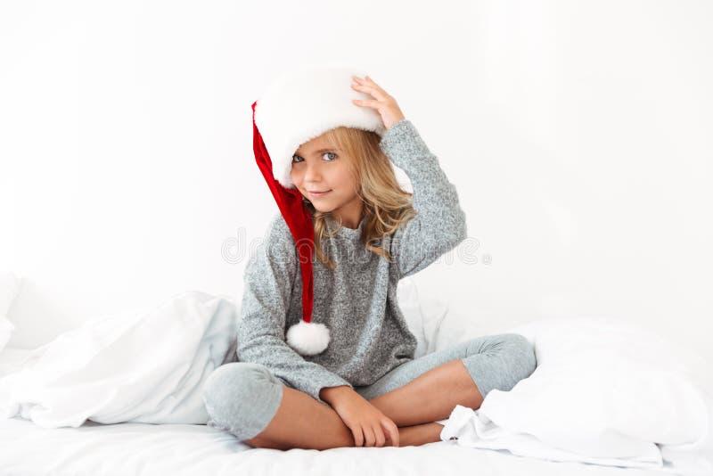 Niña linda en los pijamas grises que tocan su sombrero mullido del ` s de Papá Noel fotos de archivo libres de regalías