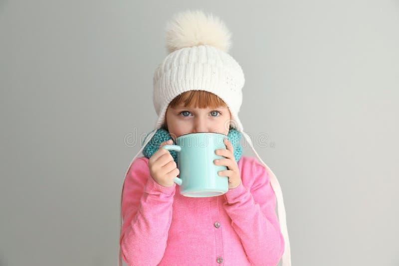 Niña linda en ropa caliente y con la taza de bebida caliente del cacao en fondo ligero fotografía de archivo