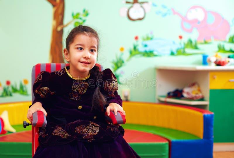 Niña linda en silla de ruedas en el centro de rehabilitación para los niños con necesidades especiales imagenes de archivo
