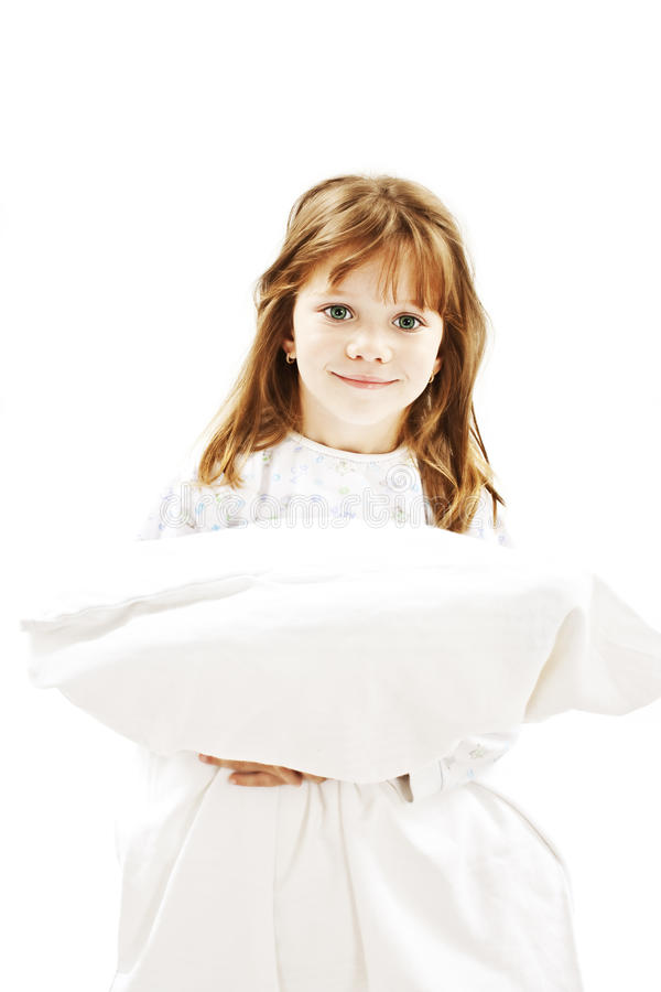 Niña linda en sus pijamas que sostienen una almohadilla fotografía de archivo libre de regalías