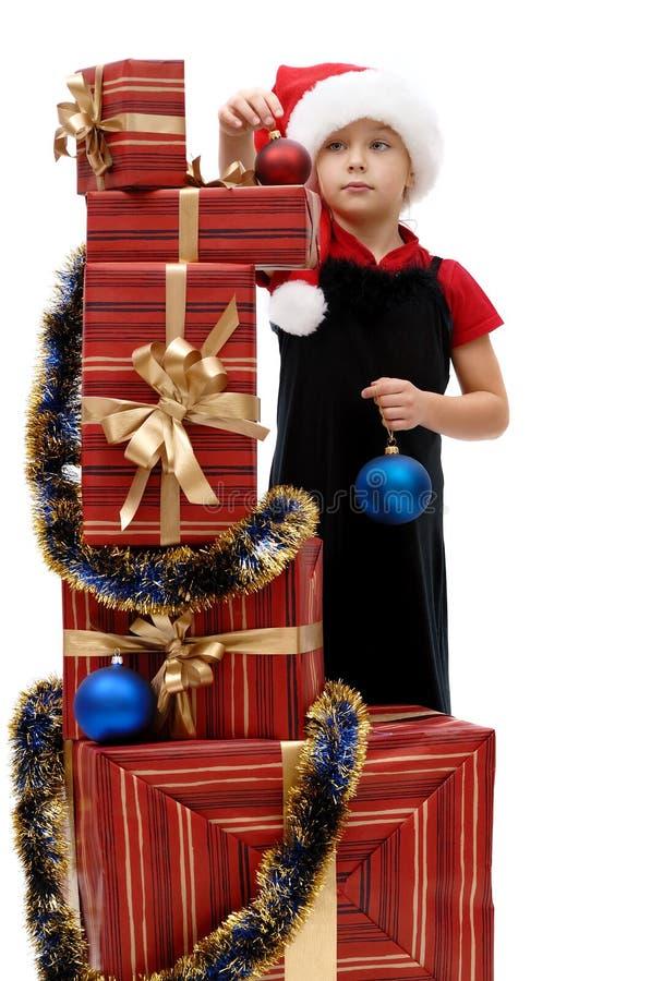 Niña linda en un casquillo con los regalos de la Navidad, aislador de Santa Claus fotografía de archivo libre de regalías