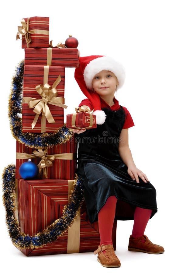 Niña linda en un casquillo con los regalos de la Navidad, aislador de Santa Claus fotos de archivo libres de regalías