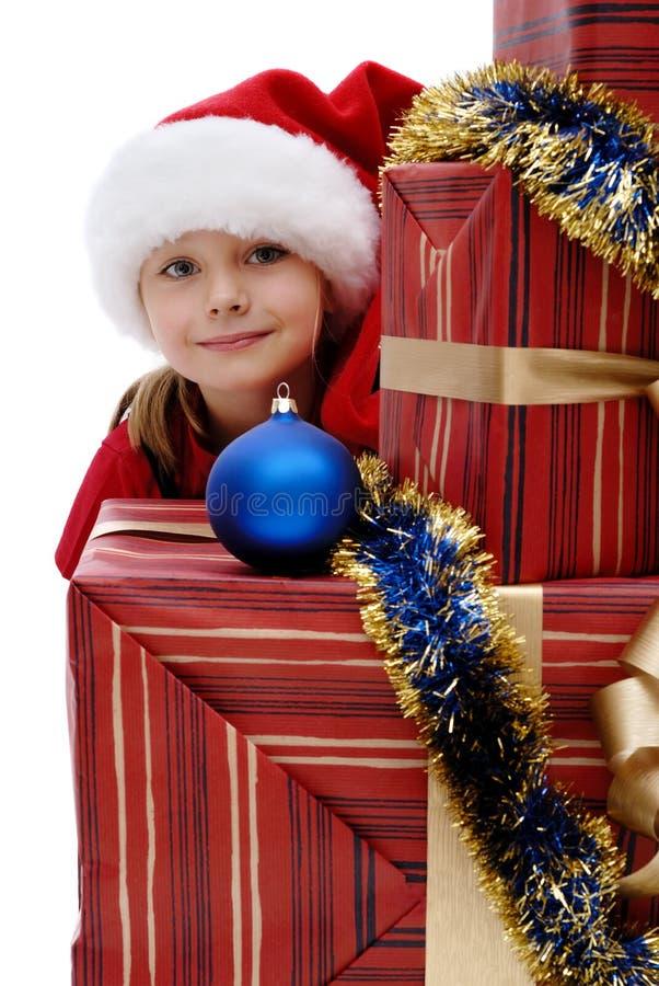 Niña linda en un casquillo con los regalos de la Navidad, aislador de Santa Claus imagen de archivo libre de regalías