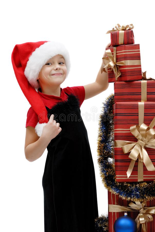 Niña linda en un casquillo con los regalos de la Navidad, aislador de Santa Claus imagen de archivo