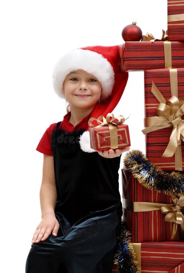 Niña linda en un casquillo con los regalos de la Navidad, aislador de Santa Claus foto de archivo