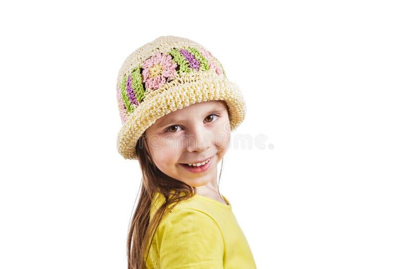 Niña linda en un sombrero de mimbre que sonríe feliz en un fondo blanco fotos de archivo libres de regalías