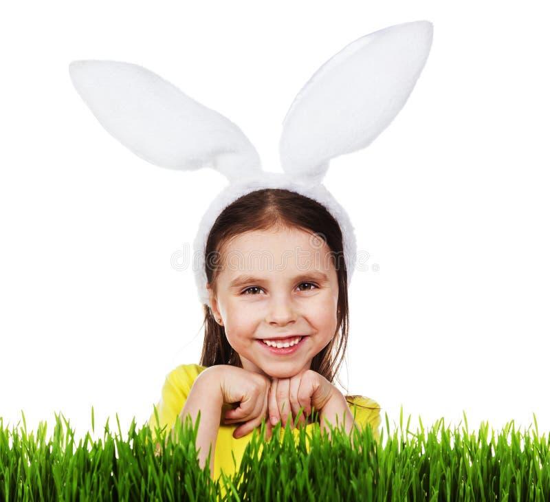 Niña linda en un traje del conejo, una hierba verde fresca en un fondo blanco foto de archivo