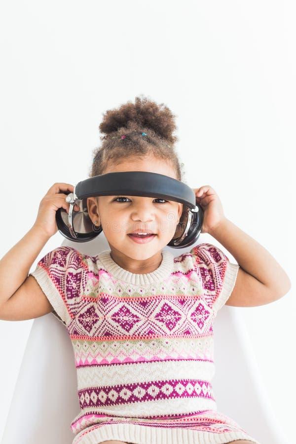 Niña linda en un vestido colorido que escucha la música con los auriculares en un fondo blanco fotos de archivo