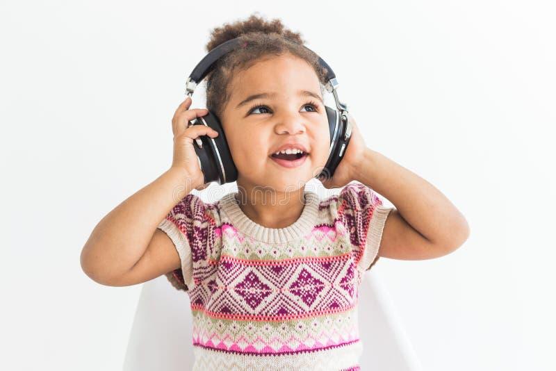 Niña linda en un vestido colorido que escucha la música con los auriculares en un fondo blanco foto de archivo