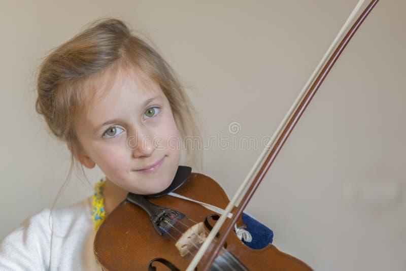 Niña linda en un vestido hermoso que toca el violín Emociones alegres y felices Entrenamiento Educación Escuela Entrenamiento est fotografía de archivo