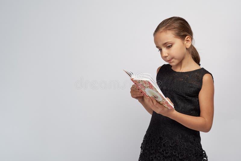 Niña linda en un vestido negro con la expresión pensativa apasionada que lee un libro fotos de archivo