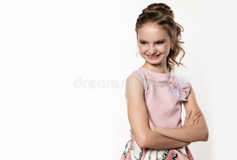 Niña linda en vestido rosado en el fondo blanco Los niños forman, diseñan concepto Espacio libre para el texto imagen de archivo