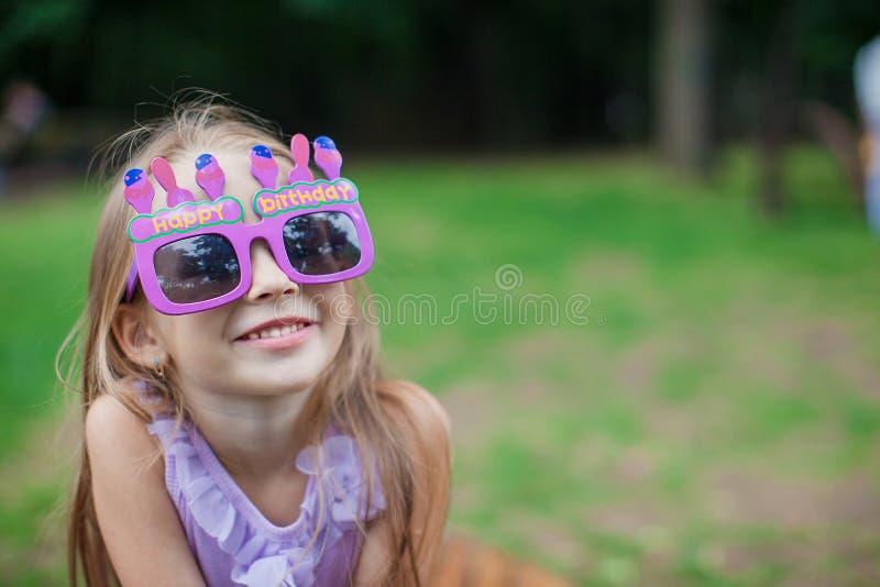 Niña linda en vidrios púrpuras del feliz cumpleaños fotografía de archivo
