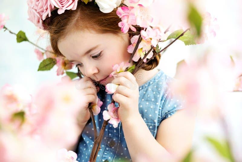 Niña linda entre las flores imagen de archivo