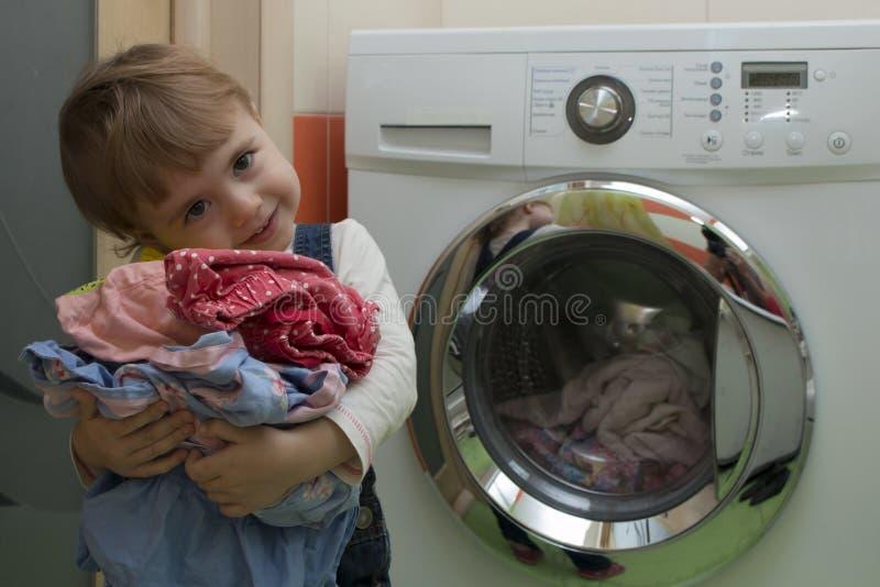 Niña linda feliz con la ropa que hace el lavadero en el interior casero imagen de archivo