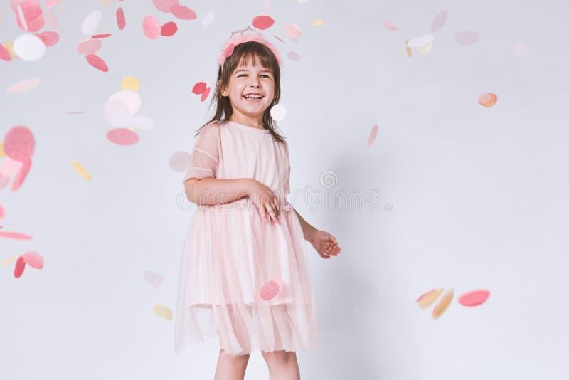 Niña linda feliz que lleva el vestido rosado en Tulle con la corona de la princesa en la cabeza en el fondo blanco que juega con  imágenes de archivo libres de regalías