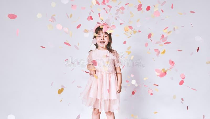 Niña linda feliz que lleva el vestido rosado en Tulle con la corona de la princesa en la cabeza en el fondo blanco que juega con  imagen de archivo libre de regalías
