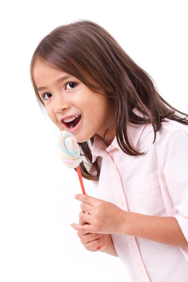 Niña linda feliz, sonriente que come el caramelo del dulce de la melcocha imagen de archivo libre de regalías
