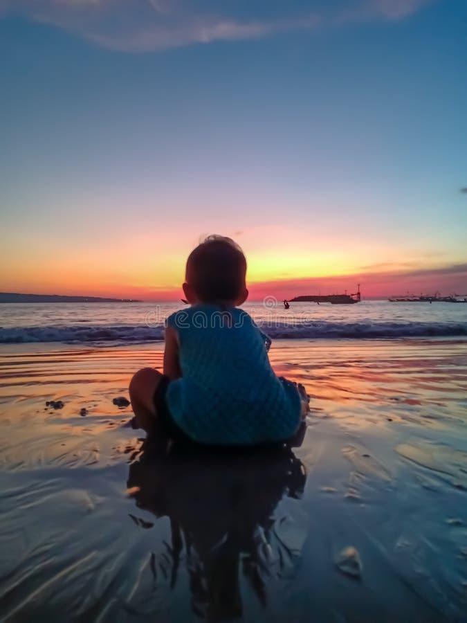 Niña linda hacer frente a la puesta del sol y a la diversión el tener en la playa imagen de archivo
