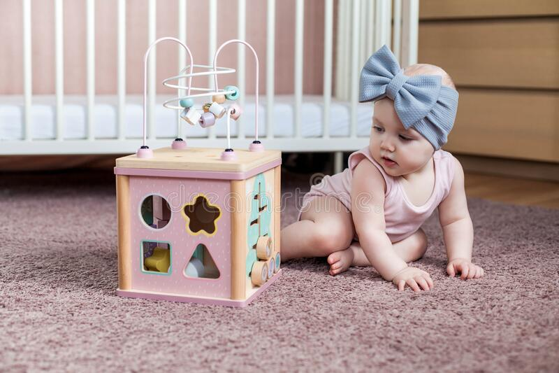 Niña linda jugando con juguete de actividad de madera fotos de archivo