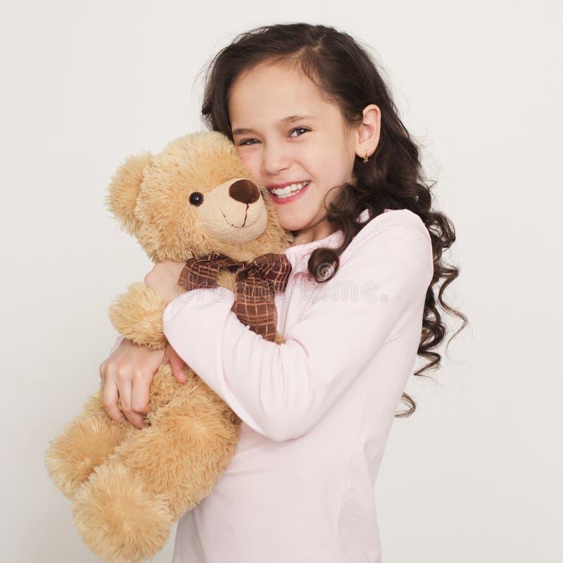 Niña linda que abraza el oso de peluche imagenes de archivo