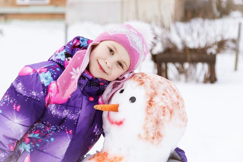 Niña linda que abraza un muñeco de nieve imagenes de archivo