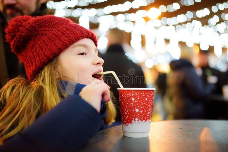 Niña linda que bebe el chocolate caliente en mercado tradicional de la Navidad Niño que goza de los dulces, de los caramelos y de foto de archivo libre de regalías