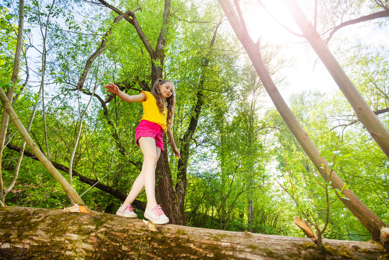 Niña linda que camina en tronco del árbol caido foto de archivo libre de regalías