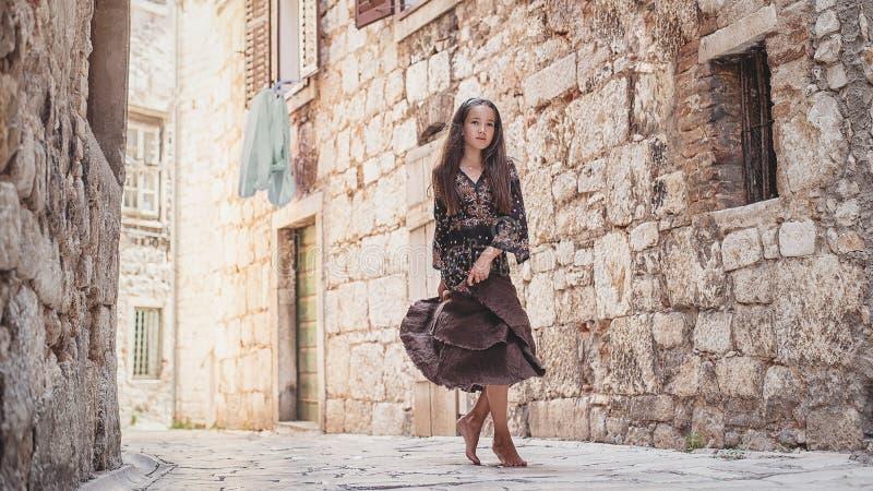Niña linda que camina a lo largo de la calle de piedra antigua en la vieja parte de la ciudad fotos de archivo libres de regalías