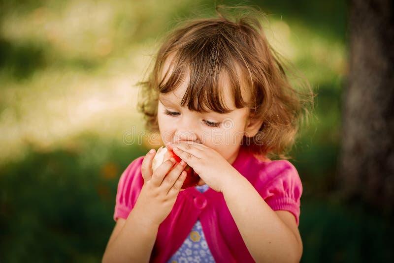 Niña linda que come la manzana en el parque imagenes de archivo