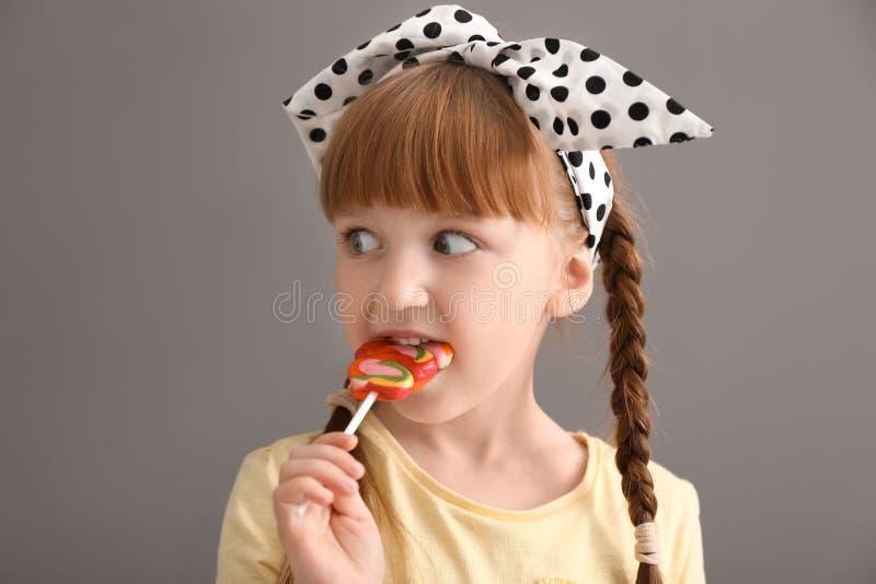 Niña linda que come la piruleta en fondo gris imagen de archivo libre de regalías