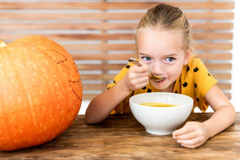 Niña linda que come la sopa de la calabaza Fondo conceptual de Halloween Comida de la comodidad de la estación del otoño fotos de archivo libres de regalías