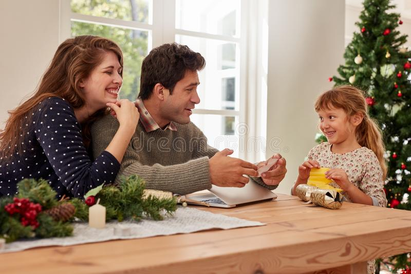 Niña linda que da el list d'envie de la Navidad a sus padres imagen de archivo